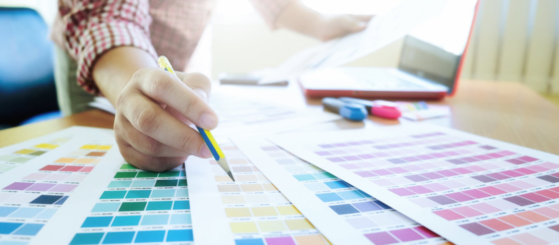 Woman working with color samples for selection. Graphic designer at work. Color swatch samples.